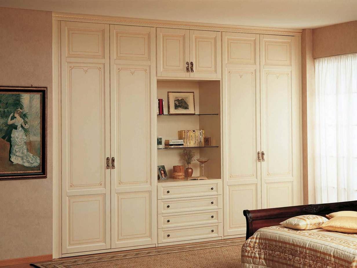 Một không gian phòng ngủ tinh tế cùng tủ âm tường nhiều ngăn kết hợp khoảng trống trang trí thêm các chậu cây nhỏ, các bức tranh...