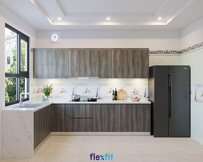 Gam màu trắng sáng đã được dung hòa bởi màu nâu gỗ trầm của tủ bếp và màu đen của tủ lạnh giúp không gian bếp hài hòa về màu sắc