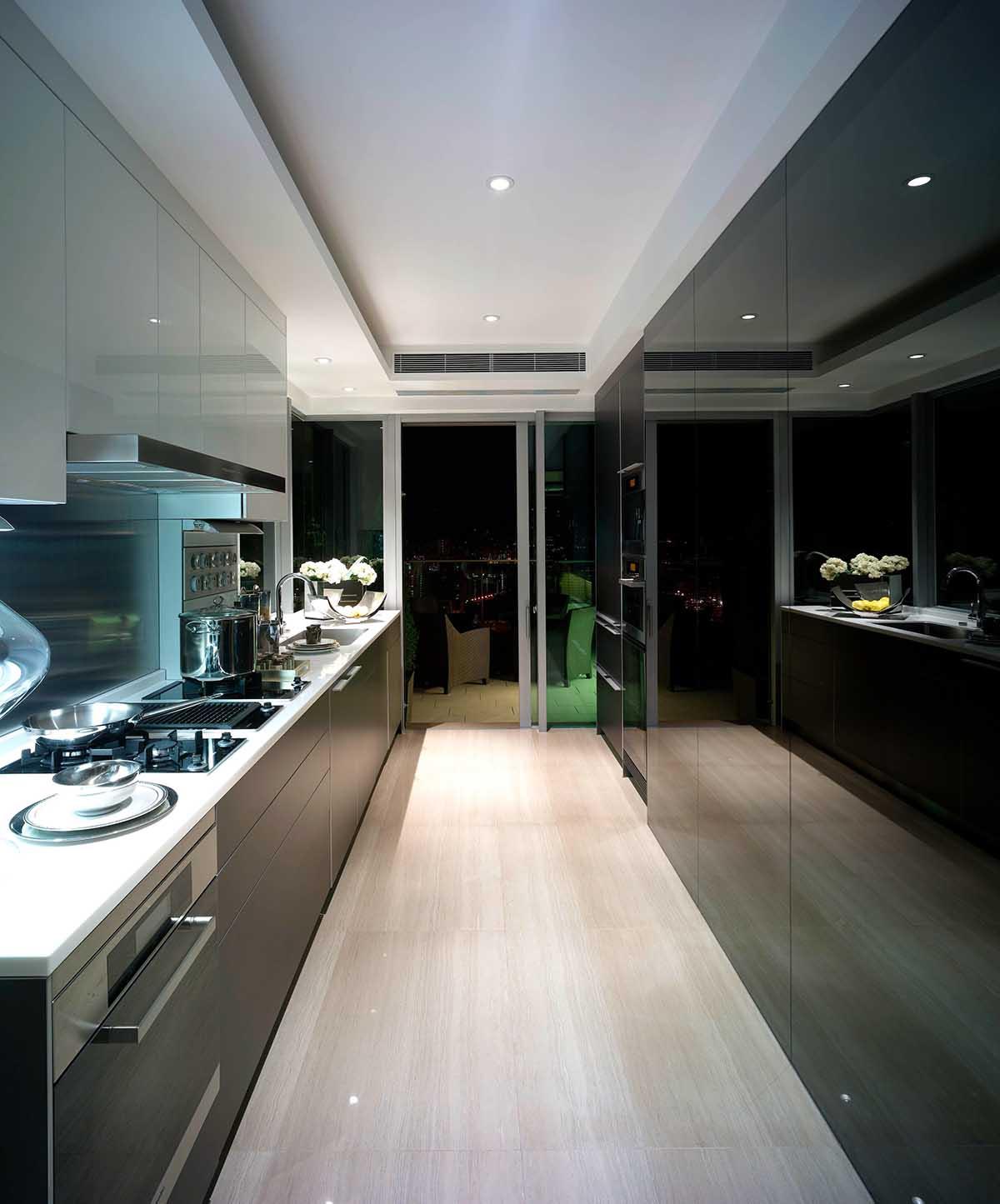 Tủ bếp chung cư song song được thiết kế theo phong cách châu Âu cùng màu ghi đen hiện đại. Một phần tủ được ốp kính tạo cảm giác không gian trở nên mở rộng, thoáng đãng hơn.