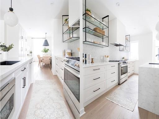 Tủ bếp song song màu trắng đồng nhất màu sơn và nội thất trong nhà. Các ngăn tủ được thiết kế tay cầm lớn, tiện sử dụng. Kệ để đồ treo tường không cánh vừa để vật dụng nhà bếp, vừa để trang trí cho bếp thêm nổi bật.