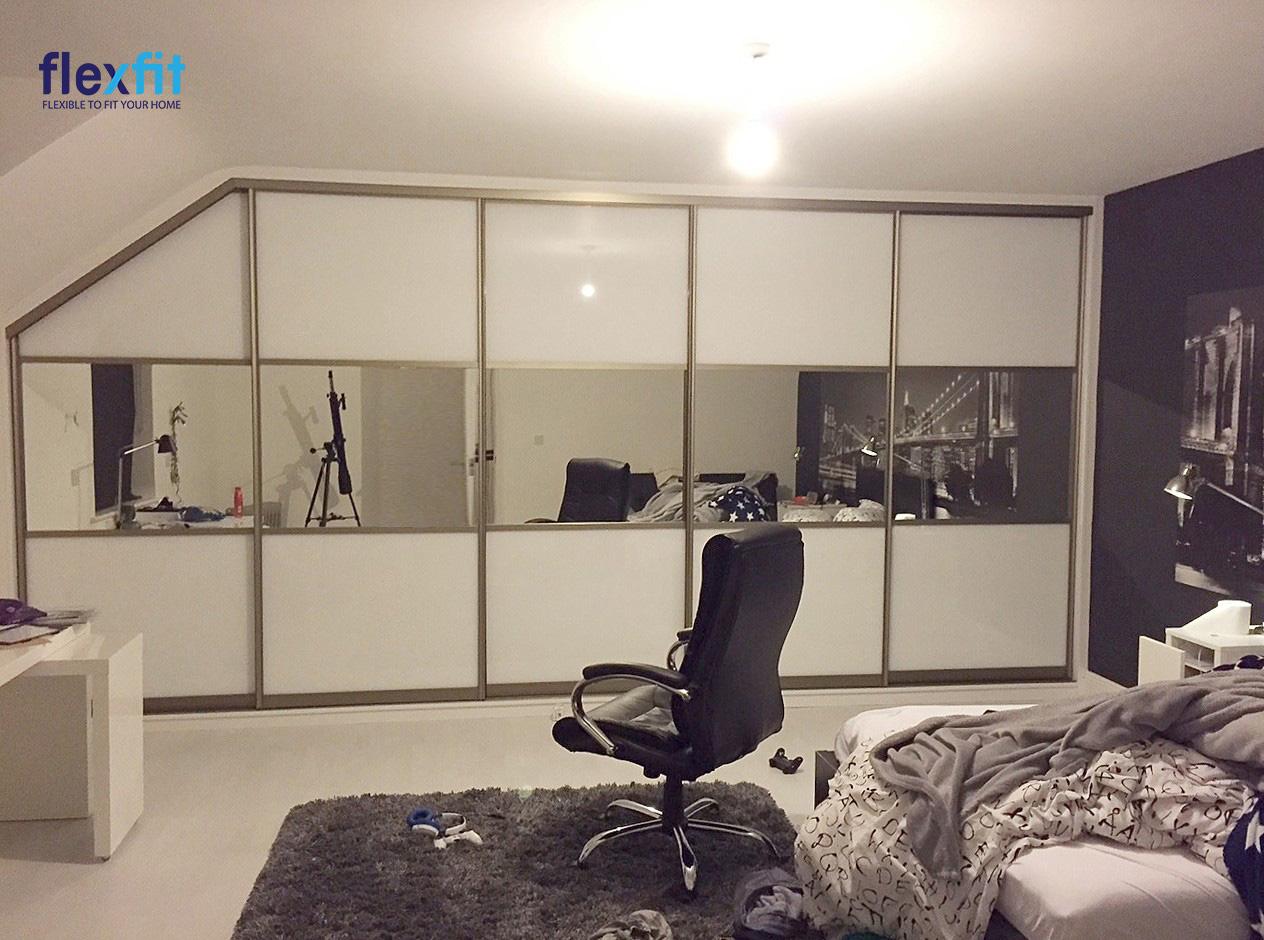 Tủ quần áo 5 cánh cửa lùa thiết kế vừa vặn với không gian, điểm độc đáo thể hiện ở chỗ lồng ghép mặt gương chạy ngang giúp căn phòng nhỏ trông rộng rãi hơn. Màu trắng sáng giúp chiếc tủ lớn không bị cồng kềnh.