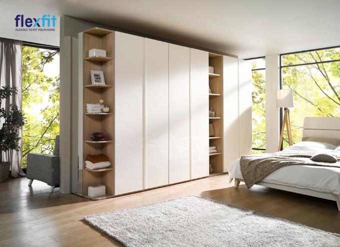 Tủ quần áo 5 cánh cửa lùa được xen kẽ bởi 2 kệ mở nhiều ngăn có thể làm giá sách hoặc bày vật trang trí giúp căn phòng sinh động hơn. Tủ có màu kem sáng phù hợp với nội thất căn phòng.