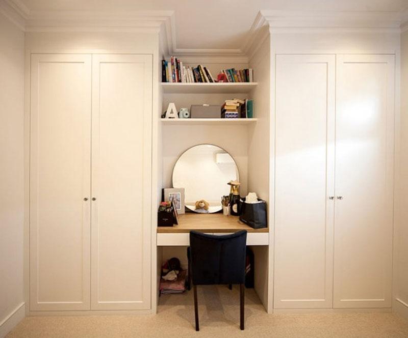 Tủ quần áo kèm bàn trang điểm được thiết kế nhỏ gọn nằm ở giữa, hai bên là tủ 2 cánh. Phía trên bàn trang điểm có các ngăn tủ không cánh để sách tiện dụng.