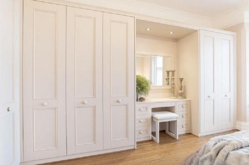 Tủ quần áo được thiết kế thành 2 phần tủ nằm 2 bên gồm tủ ba cánh và tủ 2 cánh. Ở giữa là bàn trang điểm bên trên có gắn đèn chiếu sáng. Sản phẩm phủ một màu trắng sang trọng hài hòa với màu sàn gỗ, mang đến không gian trang nhã.
