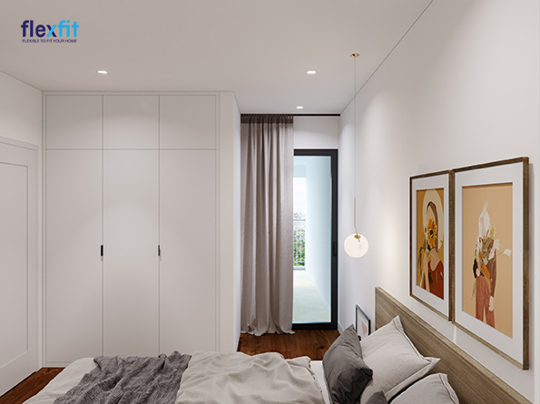 Căn phòng ngủ trở nên cao ráo, sáng, thoáng, rộng rãi hơn nhờ thiết kế tủ quần áo kịch trần 3m lõi MDF phủ Melamine, sơn tường màu trắng và cửa kính lấy sáng