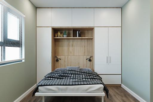 Căn phòng ngủ nhỏ vẫn đầy đủ các tiện ích nhờ sử dụng mẫu giường âm tường tích hợp hệ tủ quần áo, tủ để đồ. Bạn có thể dễ dàng gấp gọn giường khi không sử dụng thuận tiện, tiết kiệm diện tích tối đa. Ngoài ra, gam màu trắng kết hợp vân gỗ sáng của hệ giường tủ tạo cảm giác không gian thoáng đãng hơn.