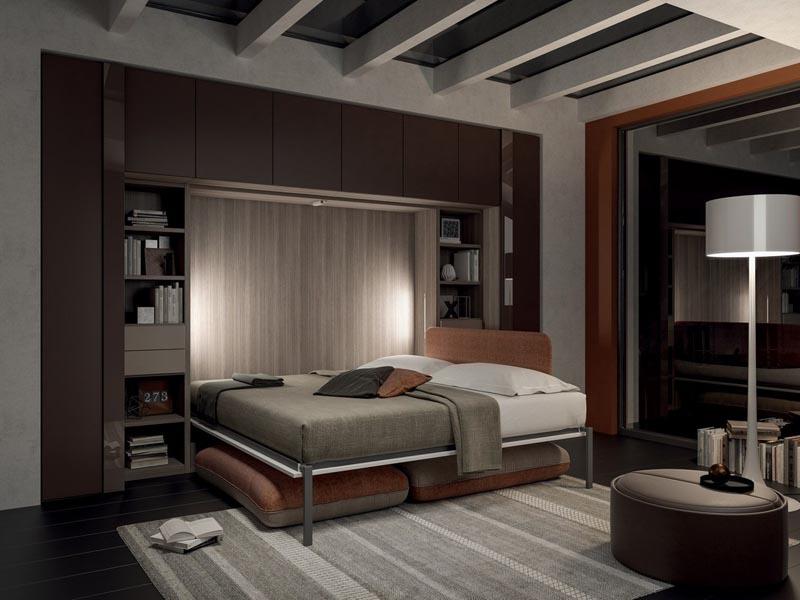 Mẫu giường âm tường tông màu nâu vân gỗ hơi trầm hài hòa với màu kệ trang trí cùng các ô tủ bên trên. Khi gấp gọn giường lại, bạn có thêm không gian để sắp xếp, bài trí các đồ dùng, vật dụng khác theo ý thích, chẳng hạn như: tấm phủ ghế sofa kèm gối ôm,...