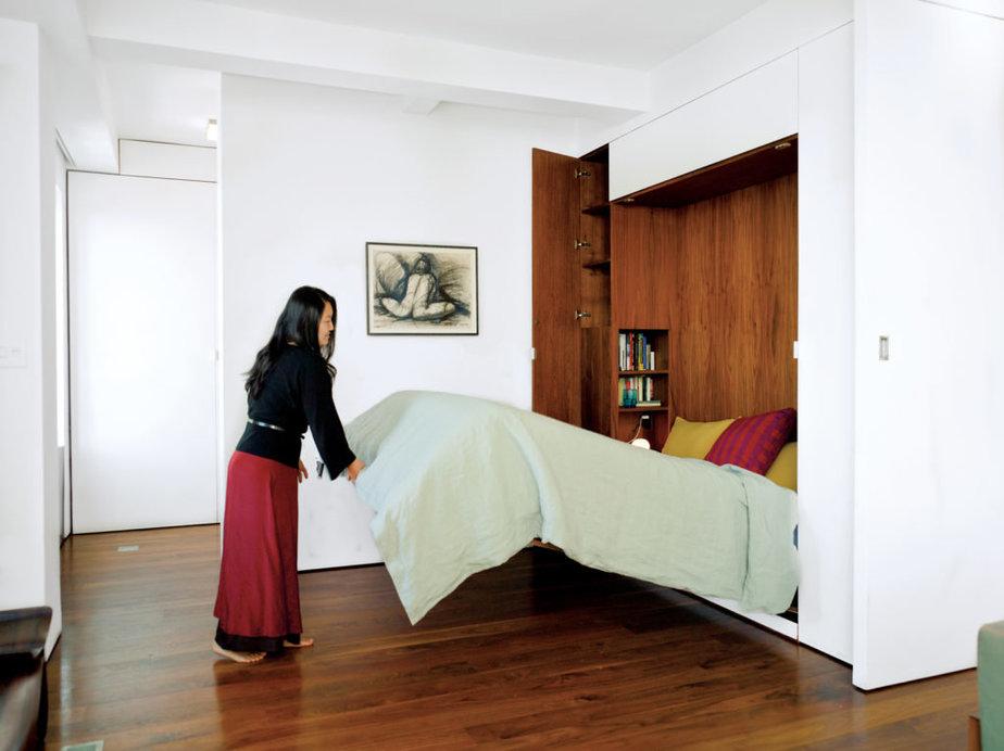 Mẫu giường âm tường - giải pháp cho phòng ngủ nhỏ dễ dàng gấp gọn khi không sử dụng này sở hữu gam màu gỗ trầm bên trong. Bên ngoài là lớp sơn trắng được tích hợp tủ quần áo tiện lợi.