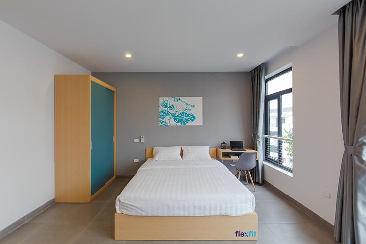 Không gian phòng ngủ pha phối các màu sắc vô cùng tinh tế tạo nên sự dễ chịu cho bất cứ ai bước vào căn phòng này. Giường ngủ gỗ vân sáng sử dụng bộ chăn ga gối đệm tông trắng hòa hợp với các mảng xanh của tủ, của tranh treo tường.