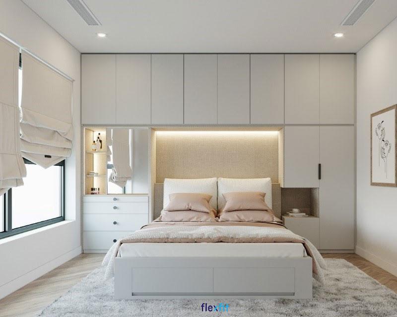 """Mẫu giường liền tủ quần áo, bàn trang điểm hiện đại, tăng tiện nghi sở hữu tông màu trắng """"không lỗi thời"""" nổi bật trên nền sàn nhà vân gỗ họa tiết."""