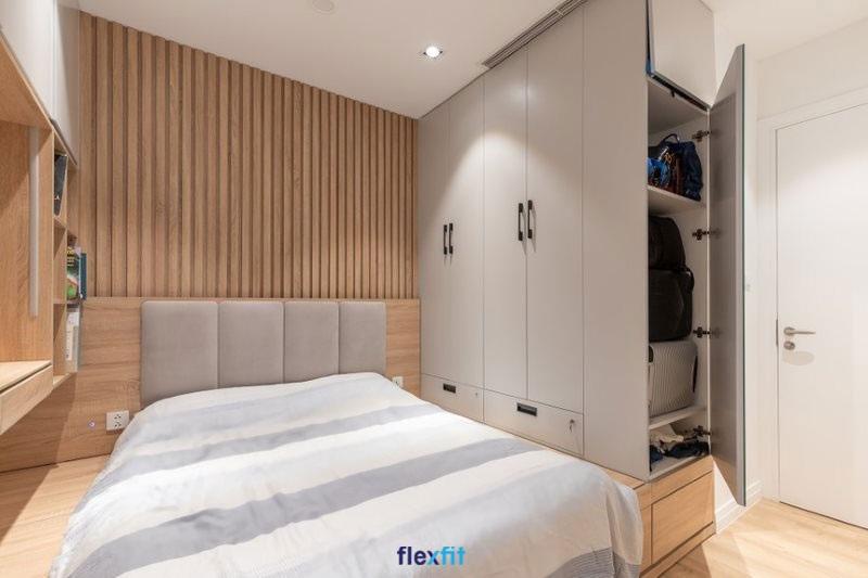 Mẫu giường liền tủ màu vân gỗ sáng kết hợp hệ thống đèn chiếu sáng giúp không gian thông thoáng hơn. Tủ quần áo, kệ trang trí được thiết kế liền kề giường ngủ tạo nên sự tiện dụng cho người dùng.