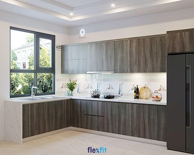 Màu vân gỗ đậm của tủ bếp nổi bật trên nền sơn trắng nhẹ nhàng, tao nhã. Tường được ốp gạch hoa văn đơn giản, tinh tế. Khu bếp nấu và vòi rửa gần cửa kính, giúp tận dụng ánh sáng tự nhiên, tránh ẩm ướt.