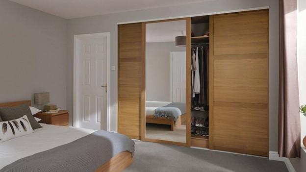 """Mẫu tủ quần áo có gương này gây """"thương nhớ"""" bởi thiết kế gương dài và rộng cùng màu vân gỗ rất tự nhiên được ghép cách điệu. Chân tủ ôm sát mặt sàn tạo sự chắc chắn và đẹp mắt hơn.Thiết kế 3 cánh tủ lùa dễ sử dụng và tối ưu không gian."""
