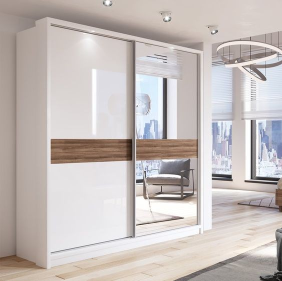 Mẫu tủ quần áo có gương này sở hữu thiết kế cánh trượt hiện đại, tiết kiệm diện tích. Tủ có màu trắng đồng điệu với màu sơn tường thêm điểm nhấn là mảng màu gỗ trầm ở giữa.