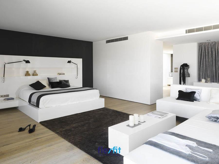 Tủ quần áo thiết kế kịch trần làm vách ngăn, tông trắng thanh lịch đồng điệu với gam màu chủ đạo của căn phòng.