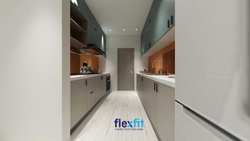 Gian bếp nhỏ ấm cúng với thiết kế tủ bếp song song sử dụng tinh tế màu tủ bếp xanh lá đậm, xám và mảng tường màu cam ở giữa.