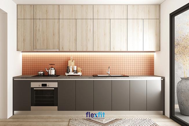 Gian bếp ấm cúng nhờ sự kết hợp tủ bếp trên màu vân gỗ sáng, màu ghi của tủ bếp dưới cùng những ô vuông nhỏ màu đỏ ốp tường ở giữa. Tủ được phân chia thành những ô tủ ngang, dọc giúp bạn để đồ theo mục đích tiện lợi.