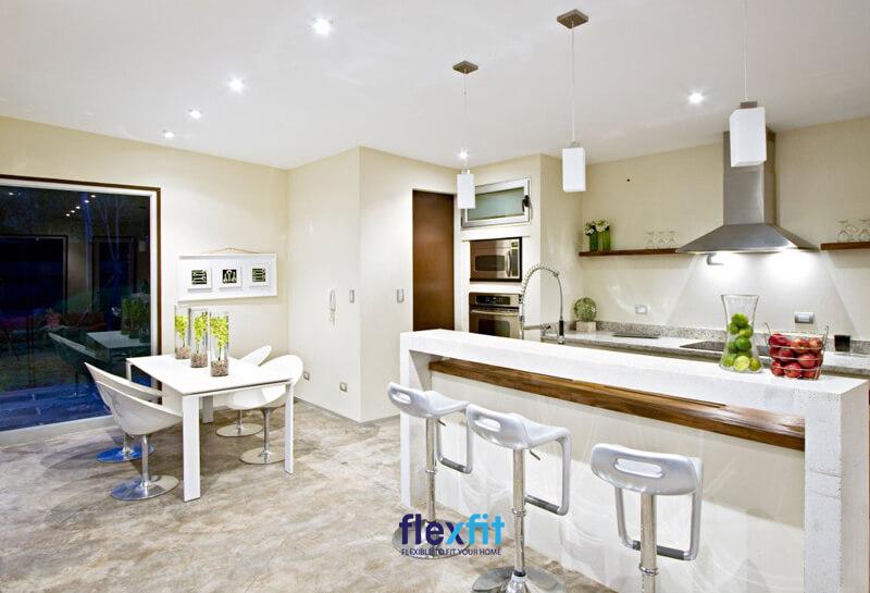 Quầy bar tông trắng thanh lịch hài hòa giữa không gian bếp sơn tường màu vàng nhạt và sàn nhà màu trung tính