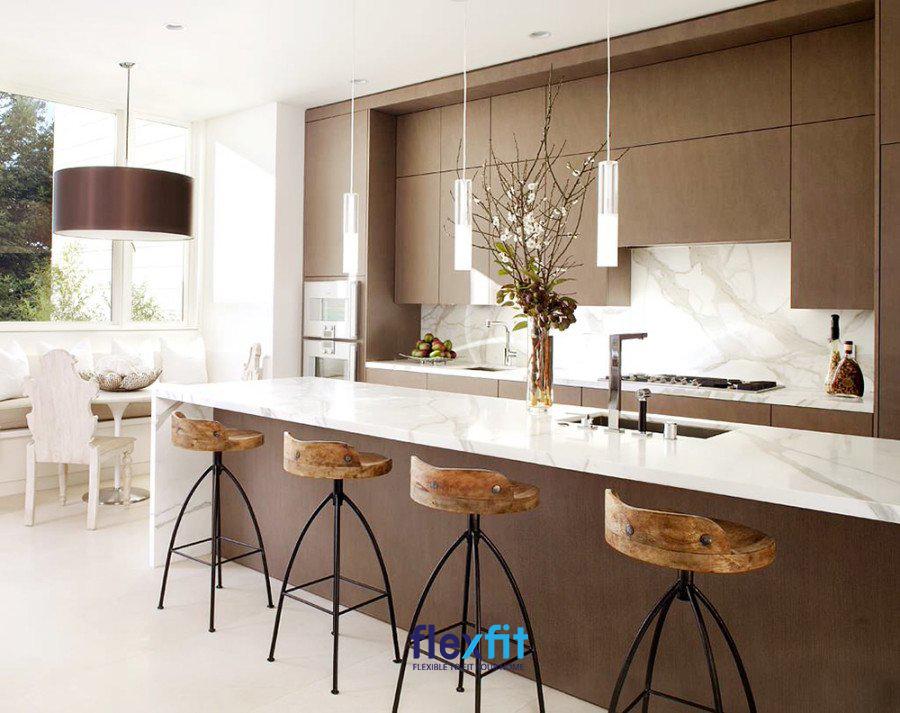 Với những nhà chung cư có kích thước lớn hơn, kiến trúc sư sẽ kết hợp quầy bar làm bàn ăn lớn ở giữa không gian bếp và khách khách. Gam màu trắng kết cùng mặt đá sẽ tạo nên không gian hiện đại.