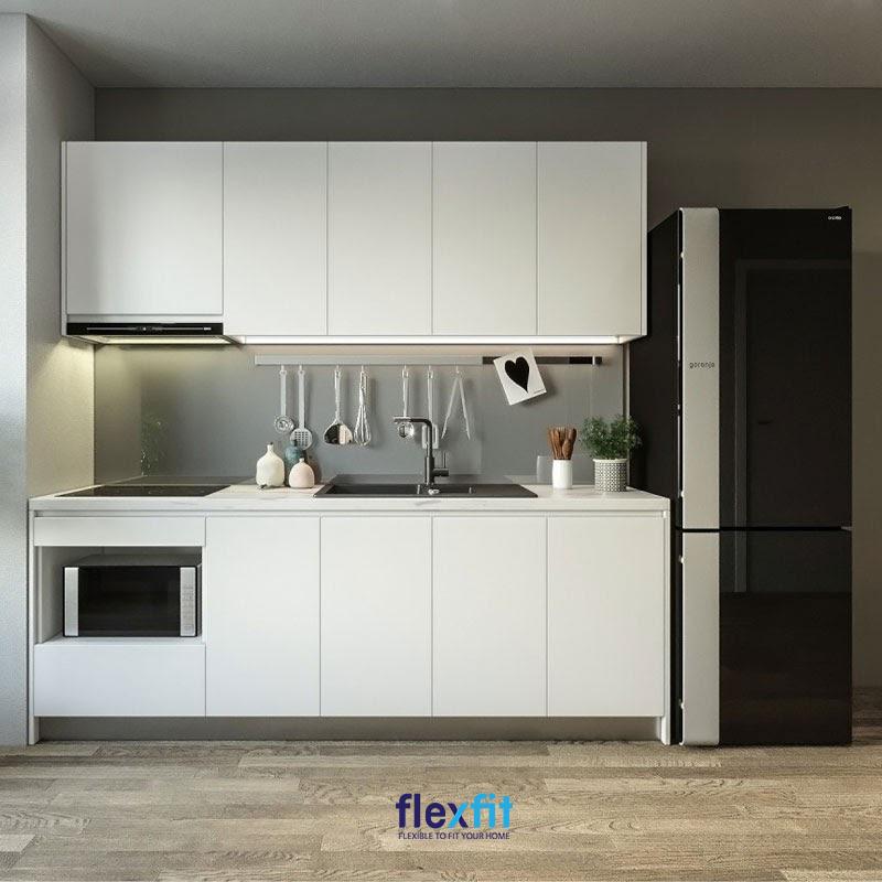 Bếp kiểu chữ I nhỏ gọn sử dụng tone màu tủ bếp trên dưới cùng màu trắng tươi sáng. Bên cạnh tủ bếp là tủ lạnh màu đen phối xám. Các gam màu này phối hợp với nhau giúp không gian nhỏ thêm thoáng rộng và mang vẻ đẹp hiện đại