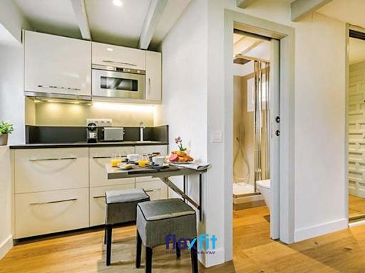 Không gian bếp nhỏ xinh với hệ tủ bếp chữ I thiết kế thông minh đầy đủ công năng cùng một bàn ăn mini treo tường mới mẻ. Bên cạnh là nhà vệ sinh có tường ngăn phân cách hai không gian