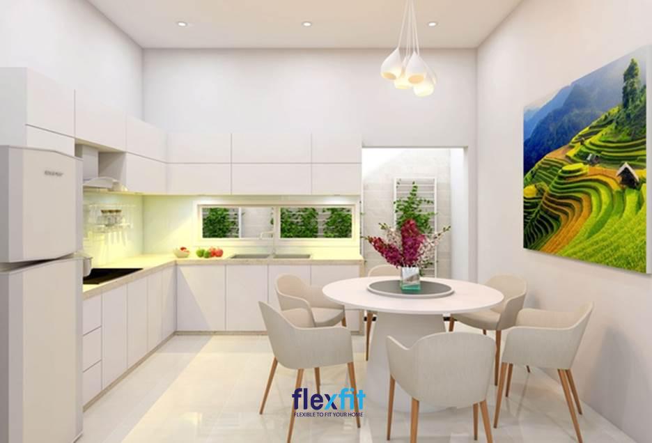 Phòng bếp nhà ống sử dụng nội thất bao phủ là gam màu trắng sáng sang trọng, giúp không gian thêm thoáng rộng. Đặc biệt, các ô cửa nhìn ra giếng trời tạo yếu tố thiên nhiên và lấy sáng hiệu quả cho căn bếp