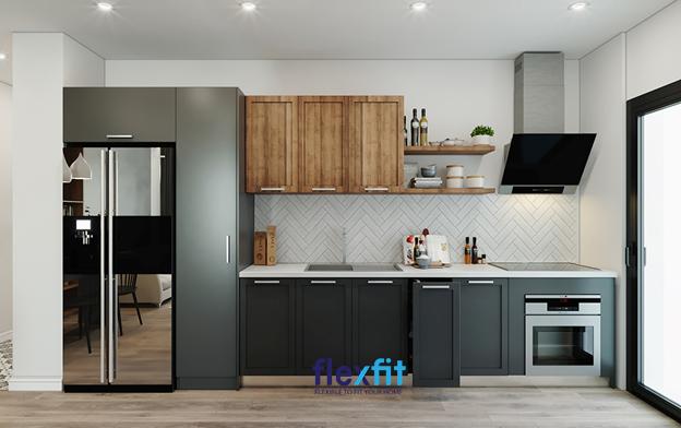 Màu nâu vân gỗ kết hợp màu ghi đậm của tủ tạo điểm nhấn cho phòng bếp. Các ngăn tủ thiết kế tay kéo tiện lợi. Kệ gỗ gắn tường phía trên có thể trang trí bình hoa hoặc để đồ dùng, gia vị tùy ý.