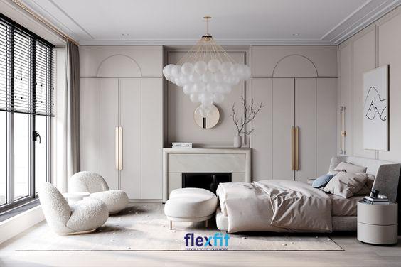 Phòng ngủ sang trọng bài trí nội thất gọn gàng, sử dụng đèn chùm, tủ quần áo tích hợp bàn trang điểm cùng bộ bàn ghế sofa nhỏ gọn